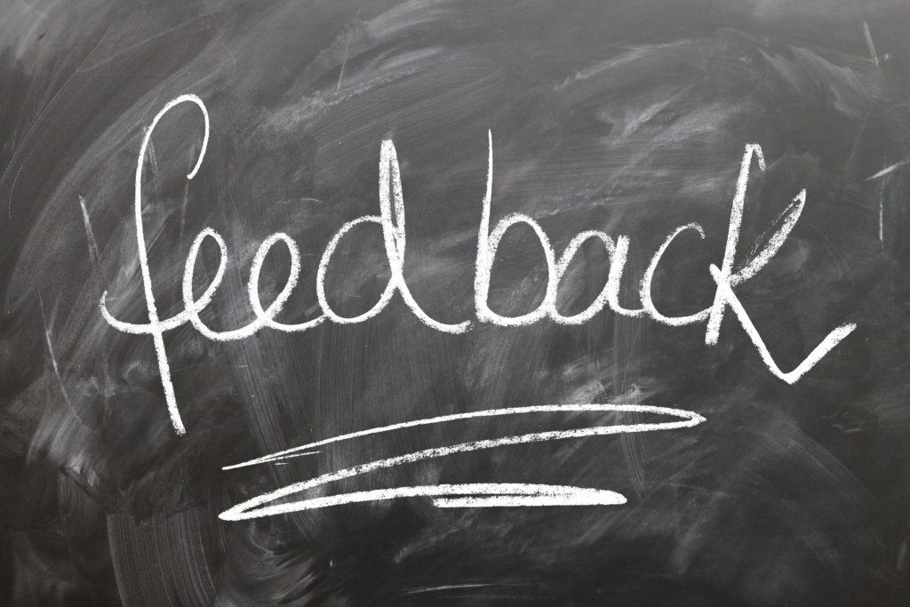 """Chalkboard with the word """"feedback"""" written on it with chalk and underlined."""
