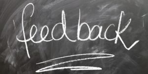 "Chalkboard with the word ""feedback"" written on it with chalk and underlined."
