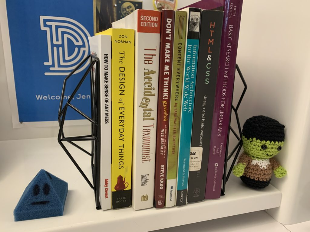 Eight books on a desk held up by bookends with a small crochet amigurumi of Frankenstein to the right.