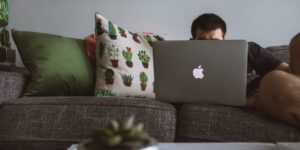 Man's face obscured by the laptop he is using on a grey living room couch.