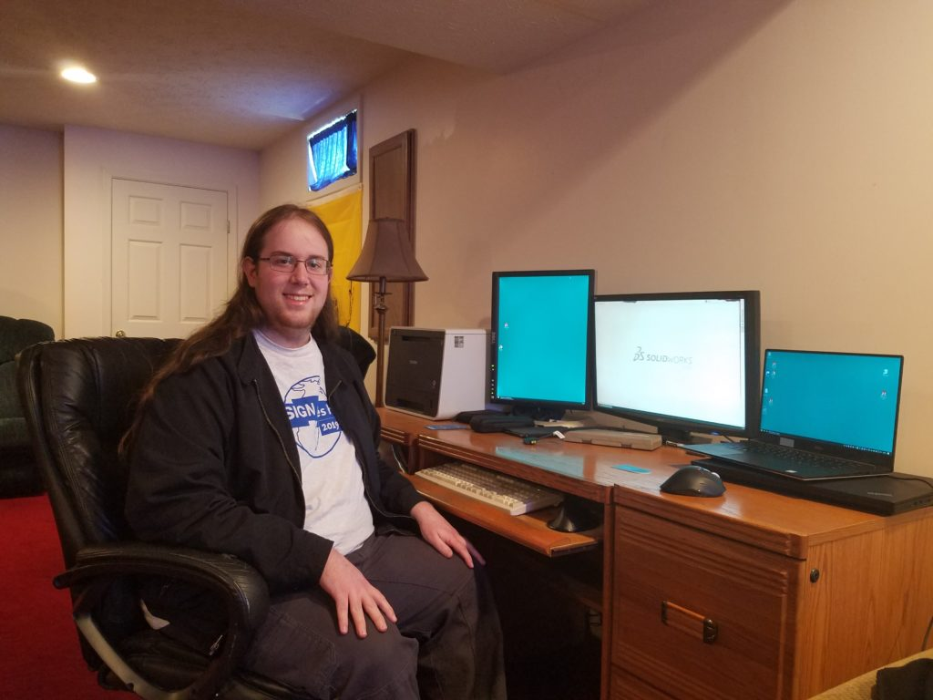 Mechanical Designer Luke Yount seated at a desk with three computer monitors.